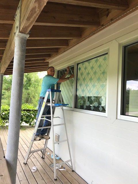man placing bird tape on windows